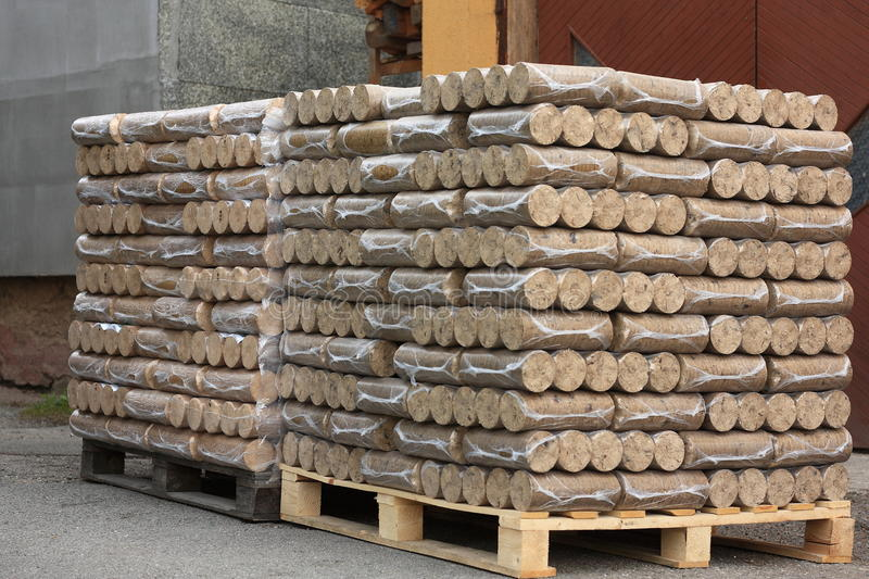 Wood briquettes on pallets. Briquettes from sawdust two pallets wrapped in plastic foil royalty free stock photos