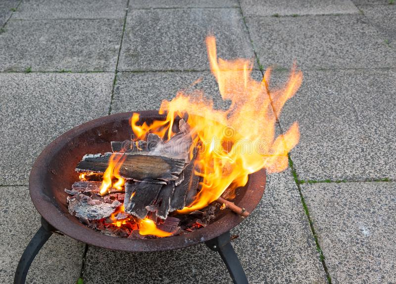 Wood burning brightly in a fire pit stock photos