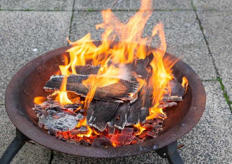 Wood burning in a metal fire pit stock photo
