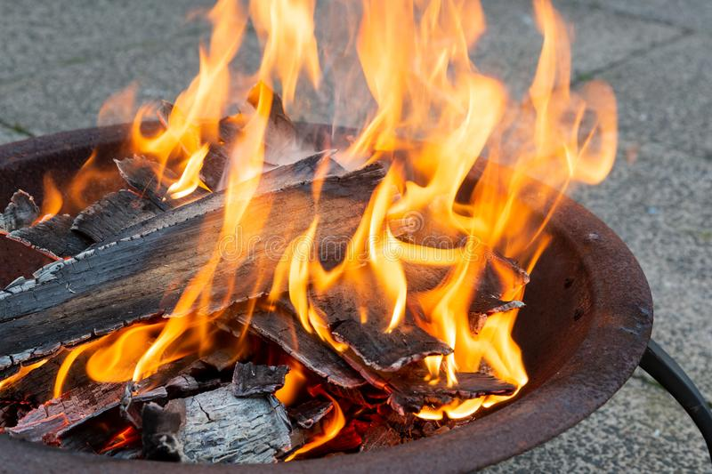 Wood burning in a metal fire pit stock photos