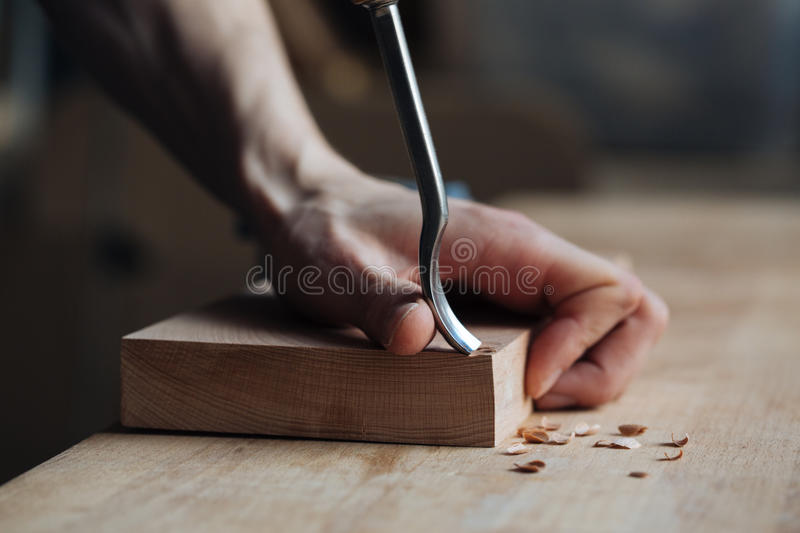 Wood carving, the master`s hands work with a wooden surface, a professional does wood crafts stock image