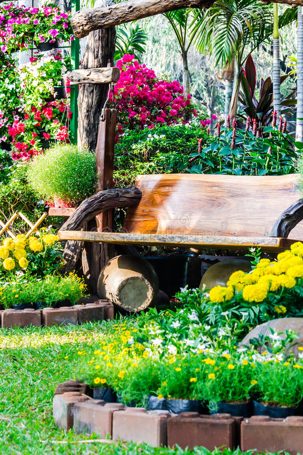 Wood chair in the flowers garden. Wood chair in the flowers garden in summer stock photos