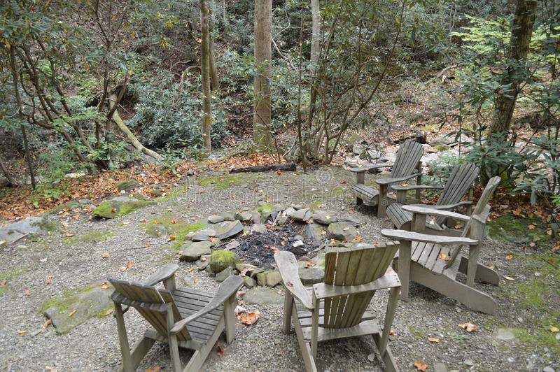 Wood chairs around fire pit. A fire pit surrounded by wooden chairs in forest stock photo