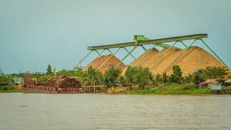 Wood chip stockpile factory on Mahakam riverbank. stock photography