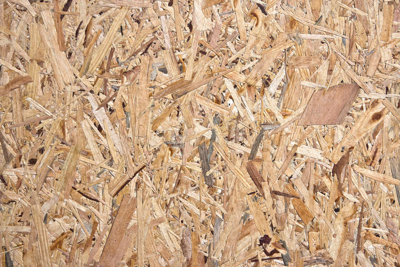 Wood chips background. Recycled and compressed wood chippings board texture stock image