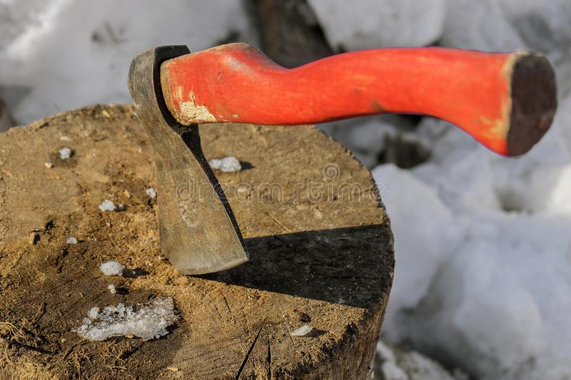 The wood chopper sticks out in wooden hemp. Ax and ax handle. Woodworking. Deforestation by a sharp axe. Ax to chop wood. Rusty. The wood chopper sticks out in stock images