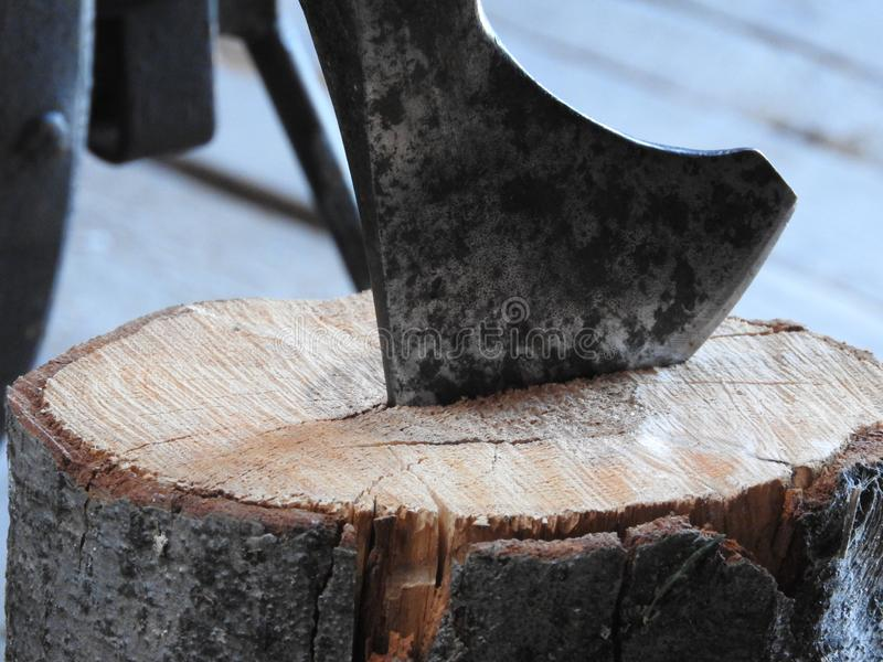 Wood chopper sticks out in wooden hemp, woodworking, deforestation by a sharp axe, axe to chop wood, rusty but very sharp forester. Wood chopper sticks out in royalty free stock photography