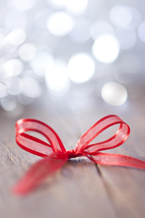 Wood Christmas Background Bow. A red bow with a festive background on wood royalty free stock photos