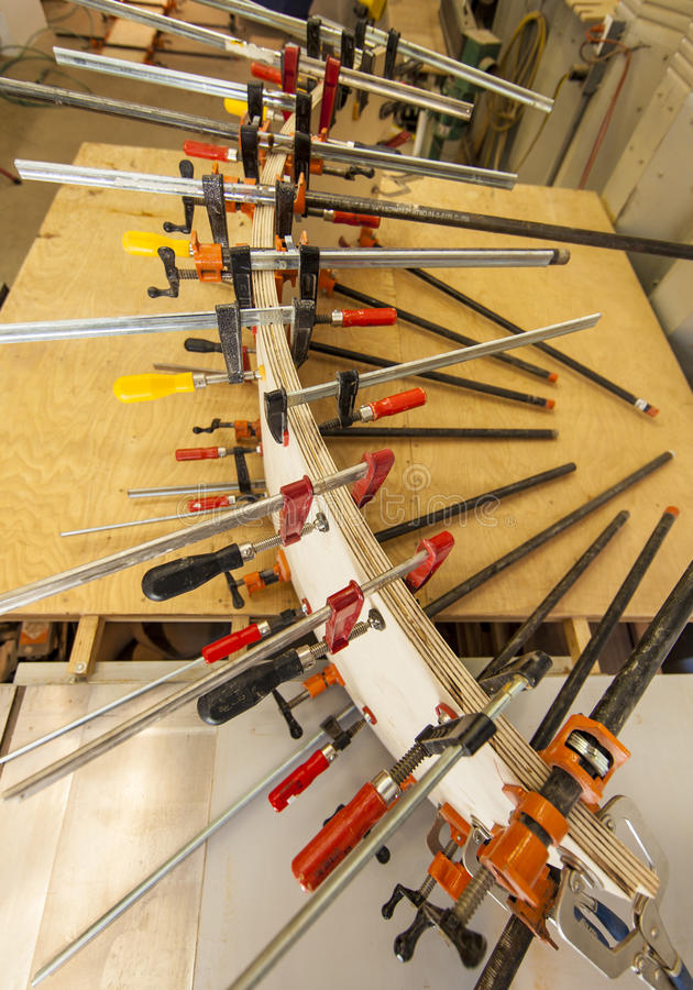 Wood clamps. Clamps holding a curved wood panel royalty free stock photos