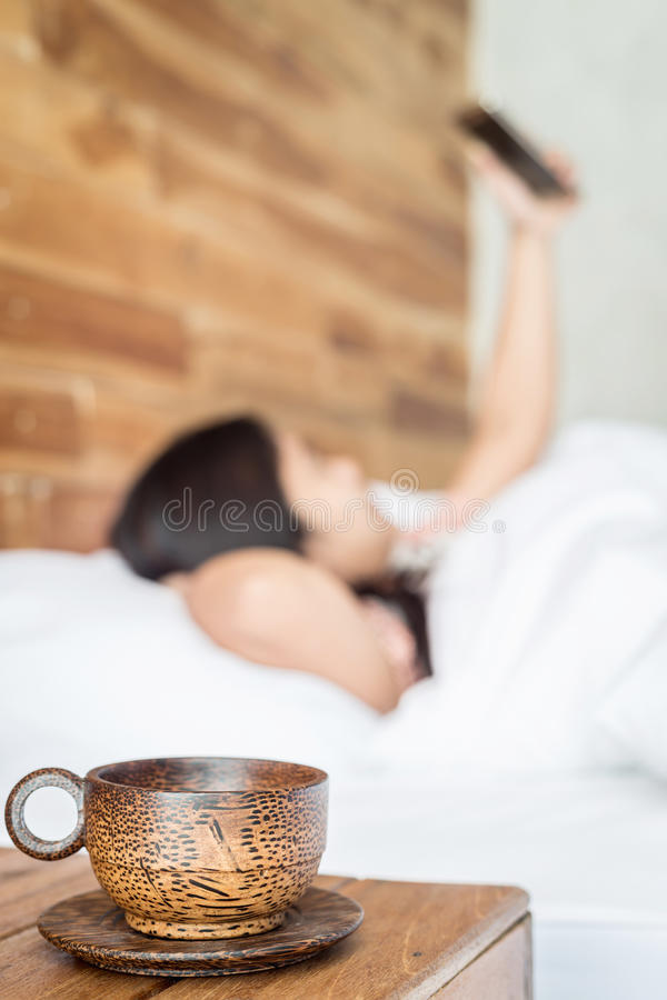 Wood coffee cup on table and women using smartphone on the bed. Close up wood coffee cup on table and women using smartphone on the bed stock image