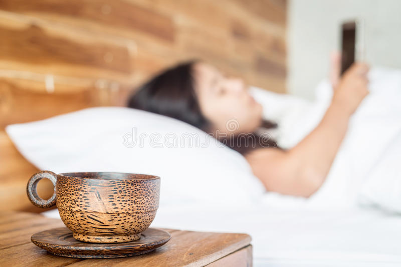 Wood coffee cup on table and women using smartphone on the bed. Close up wood coffee cup on table and women using smartphone on the bed royalty free stock image