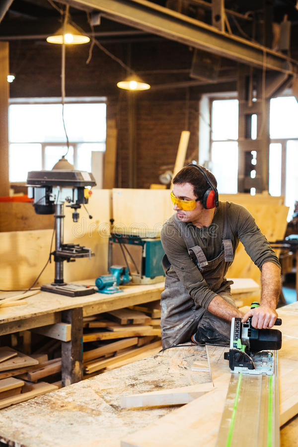Wood craft. Young craftsman using power-tool while working stock photography