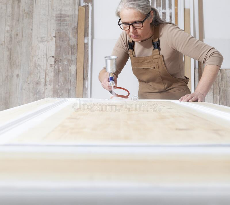 Free Wood Crafts, Woman Artisan Carpenter Painting With Spray Gun Paint White The Door In Her Workshop, Wearing Overall And Eyeglasses Stock Photo - 210592240