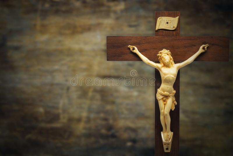 Wood crucifix on a grunge wood background with the body of Chris. T on the cross, vignette and copy space stock image