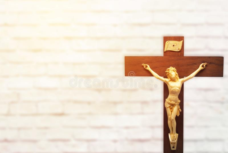 Wood crucifix on white brick wall background with the body of Ch. Rist on the cross, sunlight and copy space royalty free stock photo