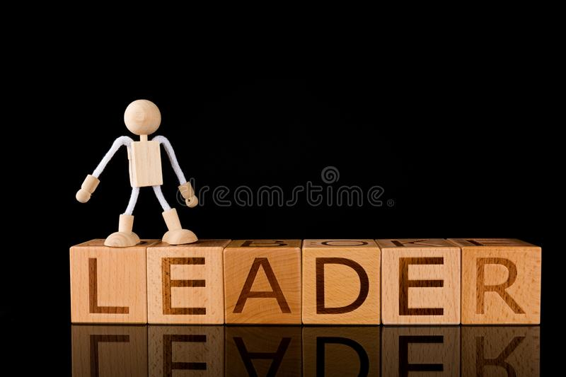 """Wood cube block with word """"LEADER"""" and Wooden Stick Figure standing. On Black Background. success concept stock photography"""