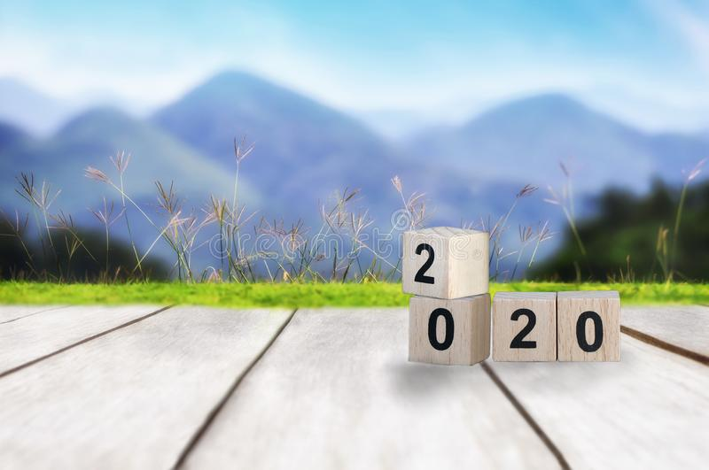Wood cube number 2020 on plank and mountain landscape view background. Happy new year concept and happy holiday idea royalty free stock photo