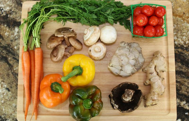 Wood cutting board in kitchen table with fresh ingredients carrot, mushroom, potatoes, tomatoes, food many colors orange, red. stock image