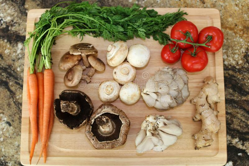 Wood cutting board in kitchen table with fresh ingredients carrot, mushroom, potatoes, tomatoes, food many colors orange, red. Wood cutting board in kitchen stock photo