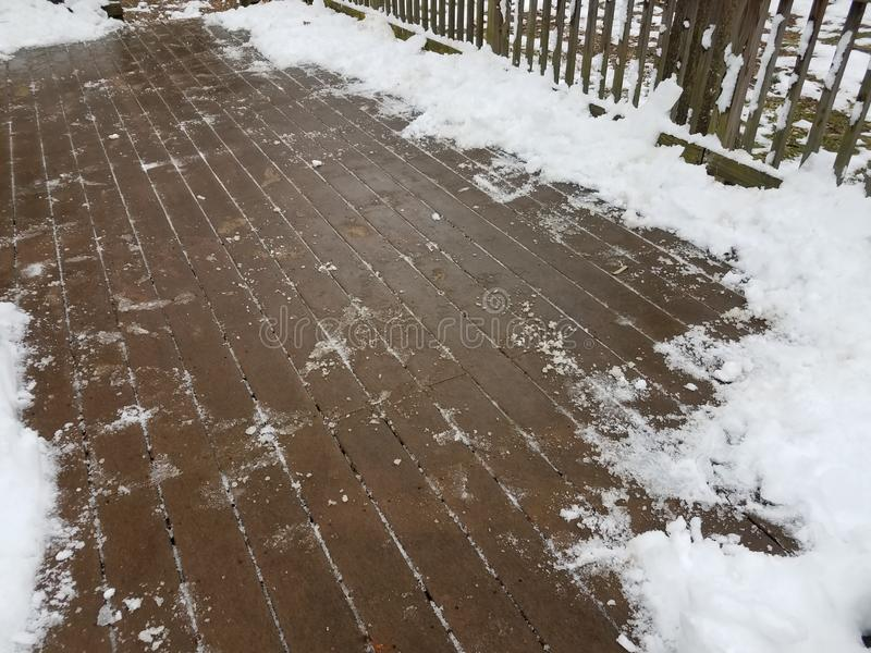 Wood deck with snow and ice partially removed. Brown wooden deck with white snow and ice partially removed stock photos