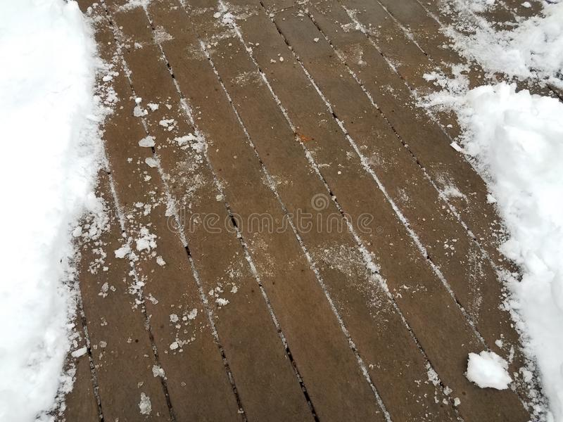 Wood deck with snow and ice partially removed. Brown wooden deck with white snow and ice partially removed royalty free stock images