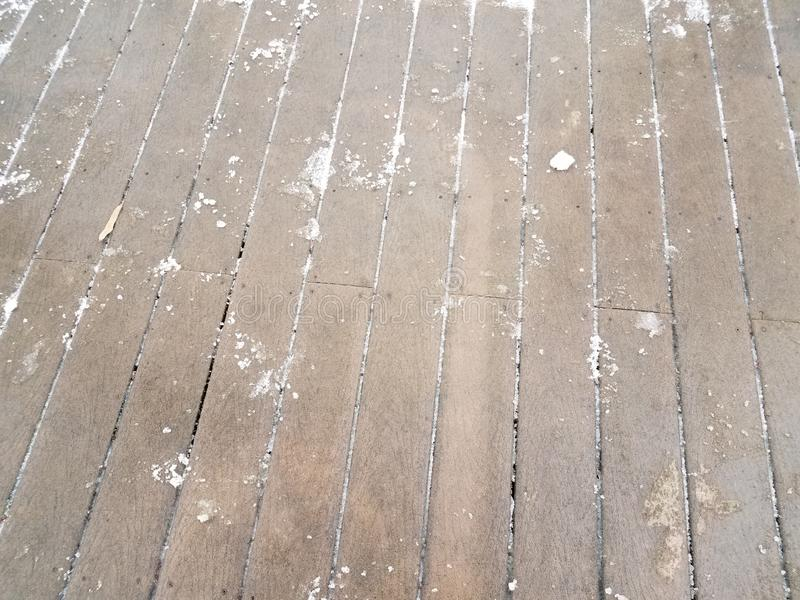 Wood deck with snow and ice partially removed. Brown wooden deck with white snow and ice partially removed stock photo