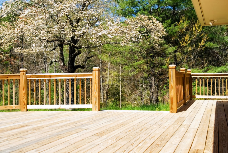 Wood deck in spring/wide. Close shot of a new wood deck with a spring Dogwood tree in the background stock photo