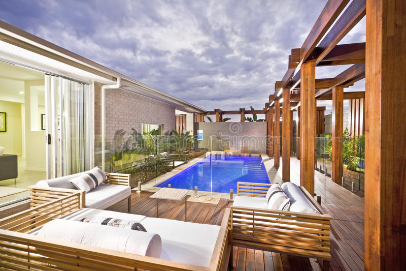 Wood decorated swimming pool area with swimming pool. Wood decorated swimming pool area with green plants and glass panel cover under the cloudy sky in a modern stock photos
