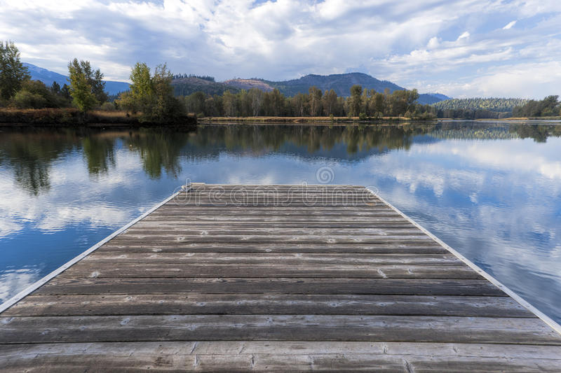 Wood dock by calm river. royalty free stock photography