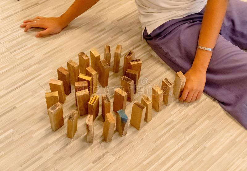 Wood domino lined up by a man`s hand royalty free stock images