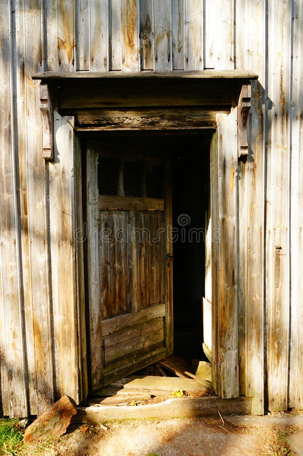 Wood door in old farm house, Norway. An old falling down farm house Telemark, Norway. Norwegian oldest wooden grey farm house. Old abandoned norwegian farm house royalty free stock photography