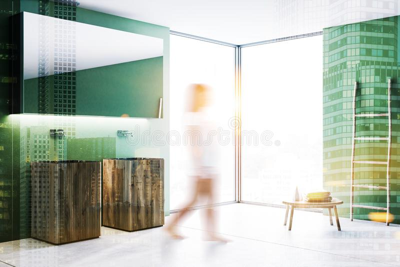 Wood double bathroom sink in green room, woman. Woman walking past wooden double sink with a long horizontal mirror in luxury green wall loft bathroom interior royalty free stock photo