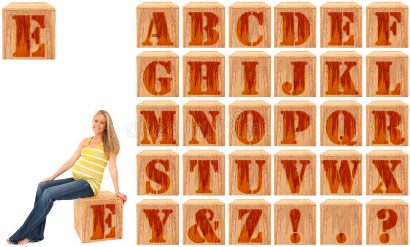 Wood Engraved Alphabet Blocks with Pregnant Woman royalty free stock photos