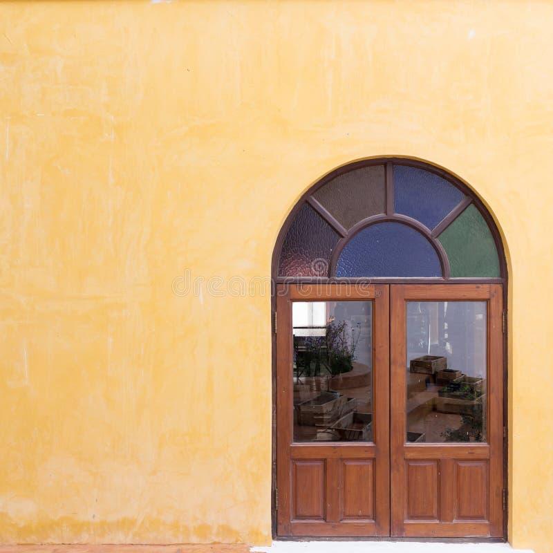 Wood fönster på den gula cementmortelväggen royaltyfri bild