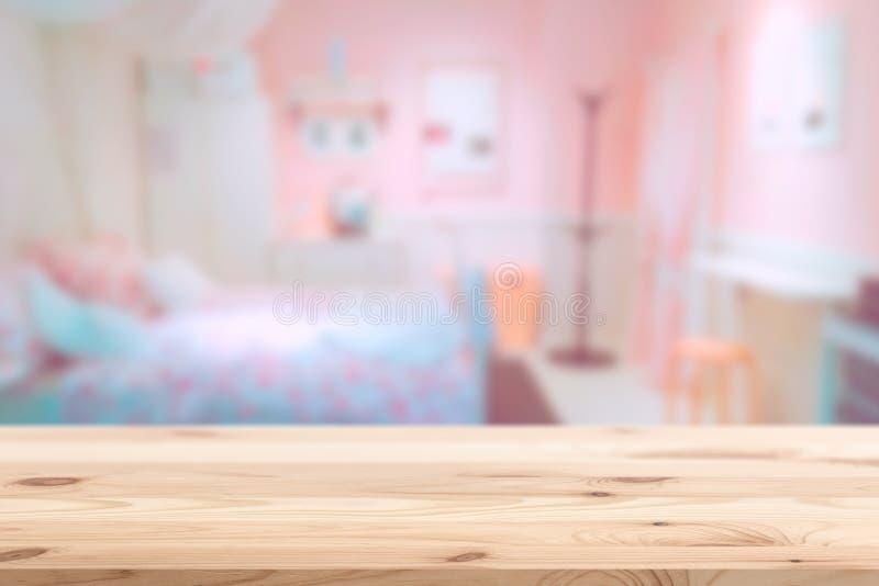 Wood förgrund med det rosa älskvärda sovrummet för suddighet royaltyfri foto