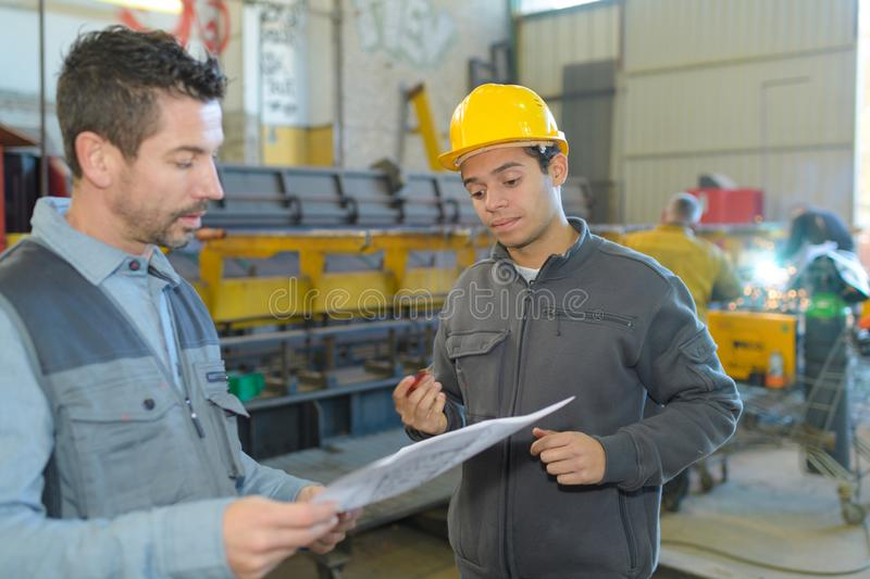 Wood factory workers discussing paperwork. Workers royalty free stock photography