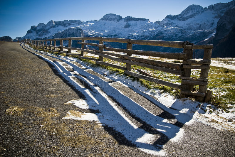 Wood Fence. In backlight with mountain landscape and snow in a sunny day - shot from an ultra wide angle - Malghe del Montasio - Italy 2007 stock image