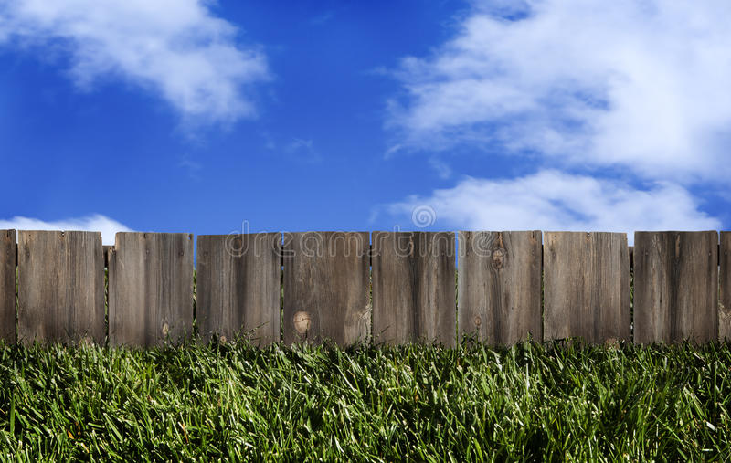 Wood Fence Blue Sky. A rustic wood fence, area for copy, with grassy area in front and blue sky with clouds behind royalty free stock image