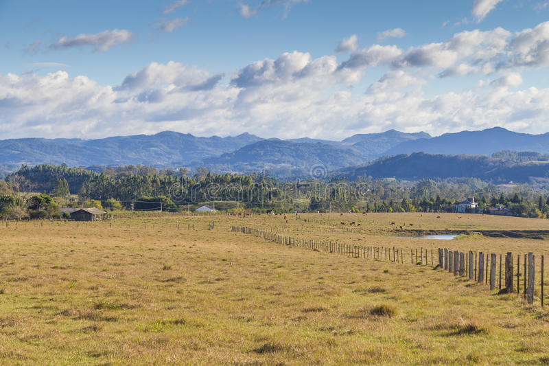 Wood fence in a farm. With mountain and cloudy sky stock photography