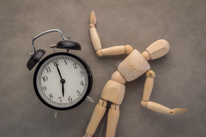 Wood figure with alarm clock. Wood figure noticing the time on an alarm clock royalty free stock photo
