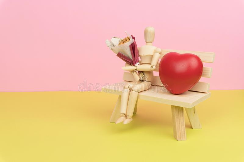 Wood figure holding a bouquet of dried flower and sitting on the wooden bench with a red love heart stock photography
