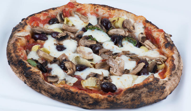 Wood Fired Artichokes Olives and Mushrooms Pizza. Close up macro of wood fired mushrooms, olives, cheese and artichokes pizza royalty free stock images
