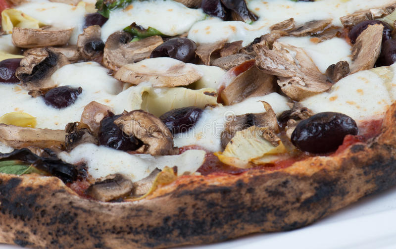 Wood Fired Artichokes Olives and Mushrooms Pizza. Close up macro of wood fired mushrooms, olives, cheese and artichokes pizza stock photography