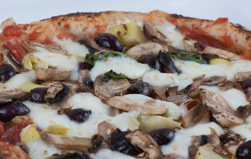 Wood Fired Artichokes Olives and Mushrooms Pizza. Close up macro of wood fired mushrooms, olives, cheese and artichokes pizza stock photos