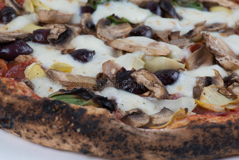 Wood Fired Artichokes Olives and Mushrooms Pizza. Close up macro of wood fired mushrooms, olives, cheese and artichokes pizza stock image