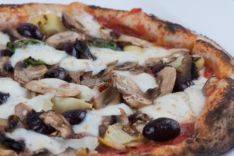 Wood Fired Artichokes Olives and Mushrooms Pizza. Close up macro of wood fired mushrooms, olives, cheese and artichokes pizza royalty free stock photography