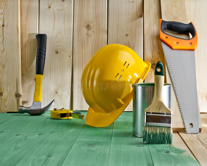 Wood floor with a brush, paint, saw and helmet. Green wood floor with a brush, paint, saw and yellow helmet royalty free stock photo