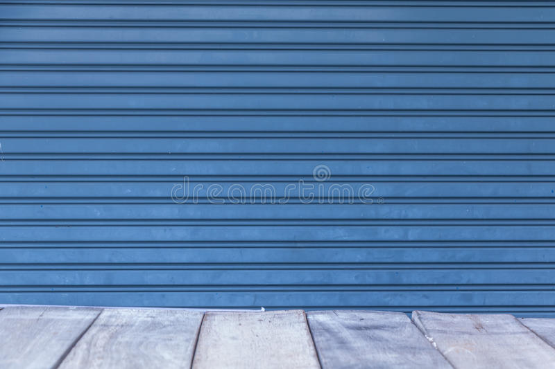 Wood floor in perspective with backdrop metal roller door. Background royalty free stock photography