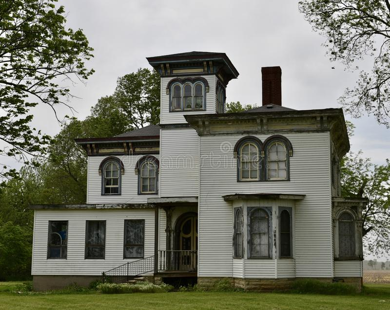 Wood Framed Italianate. This is a Spring picture of a house under rennovation on a cloudy day, located in Momence, Illinois in Kankakee County. This wood framed stock image