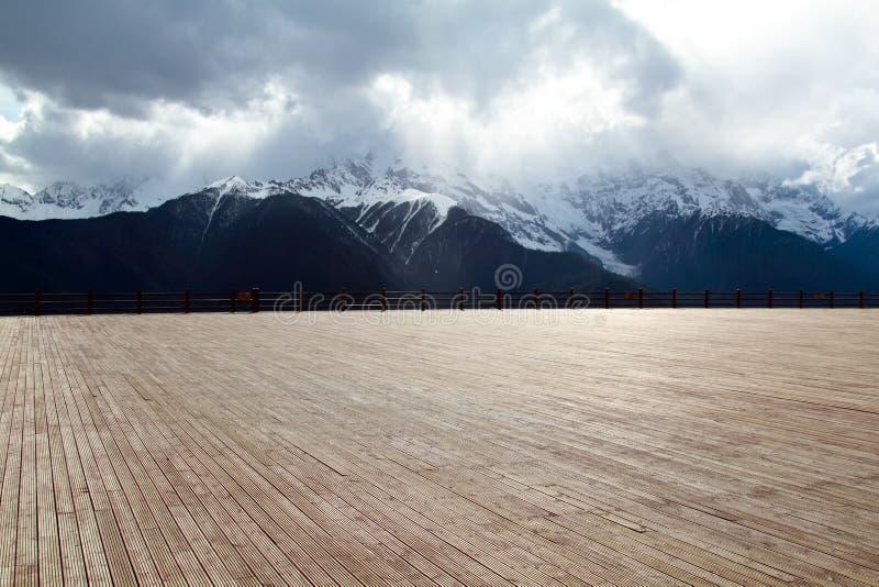 Wood golv med bakgrundsberg royaltyfria foton